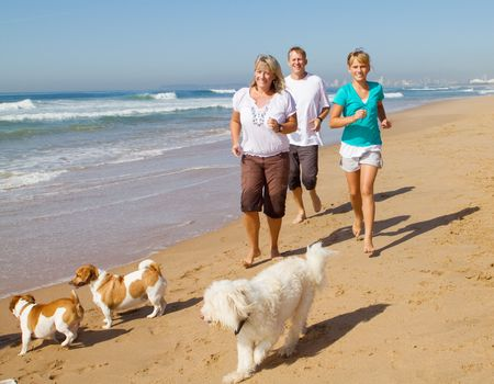 athletic activity: fit family jogging on beach Stock Photo
