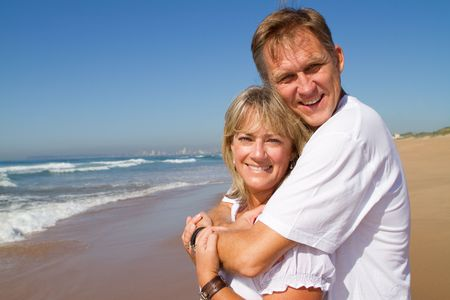 adult dating: attractive senior couple  hugging on beach