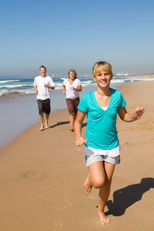 teen running on beach with parents photo