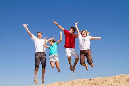 家族 4 人ビーチでジャンプ