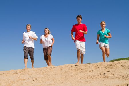 active family running on beach photo