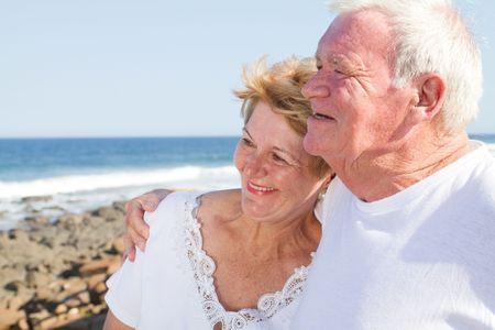 loving senior couple embrace on beach Stock Photo