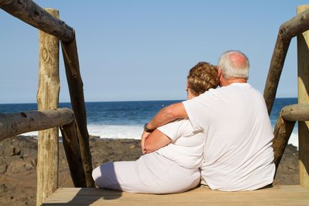 snuggle: senior couple cuddling on beach stairs