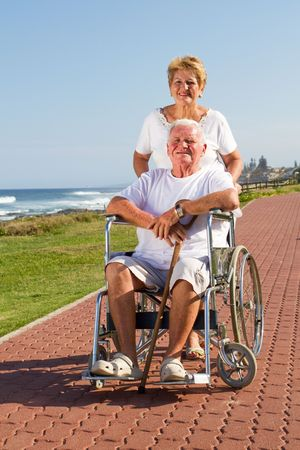caring senior wife pushing happy husband in wheelchair photo