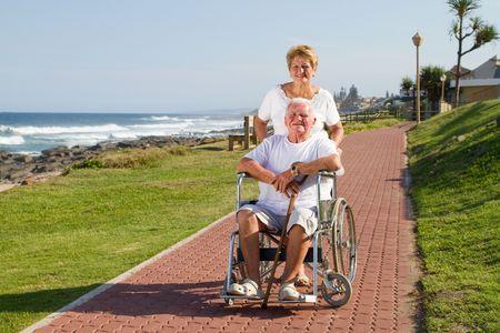 happy senior wife pushing elderly husband in wheelchair photo