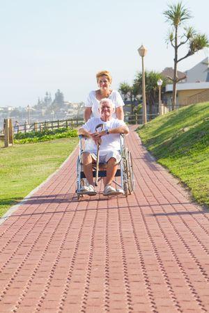 caring wife pushing husband in wheelchair  photo