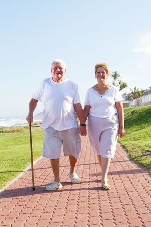 senior citizens: senior couple walking on beach front