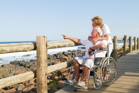 wheelchair man: tender senior couple on beach