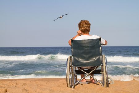 lonely woman in wheelchair on beach photo
