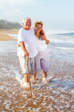 senioren wandelen: gezonde senior paar wandelen op het strand