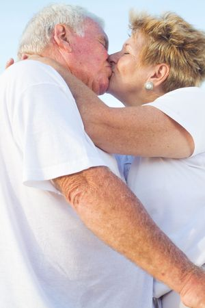senior couple kissing outdoors photo