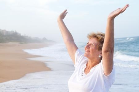 senior woman worshipping on beach photo