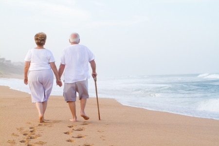 an elderly couple: couple holding hands and walking on beach