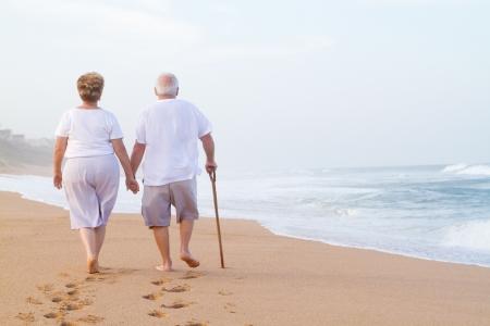 senioren wandelen: paar hand in hand en wandelen op het strand