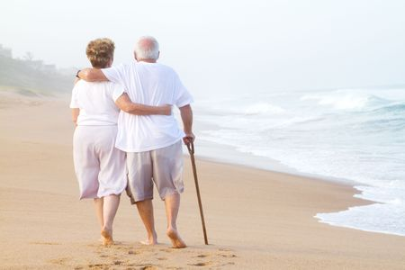 elderly couple strolling on beach photo