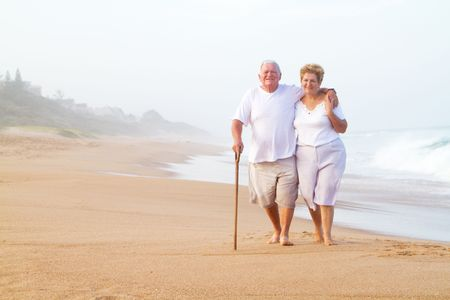 old people walking: senior couple walking on beach