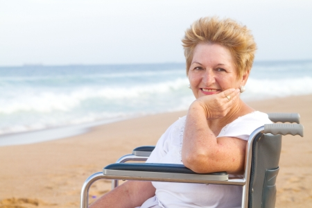 happy woman in wheelchair on beach photo