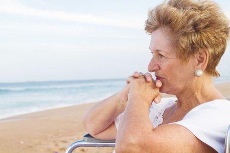 thoughtful senior woman in wheelchair photo