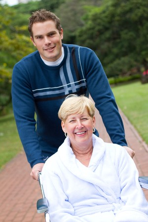 operation gown: kind son pushing sick mmother in wheelchair  Stock Photo