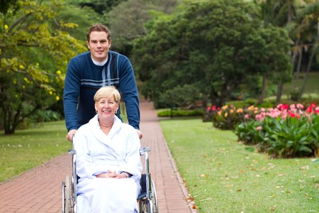 operation gown: happy wheelchair mother with caring son Stock Photo