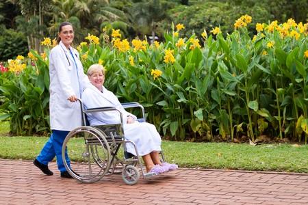 nurse pushing happy wheelchair patient photo