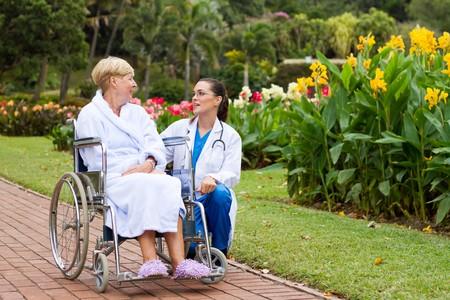 persona en silla de ruedas: joven enfermera que hablar con el paciente de silla de ruedas