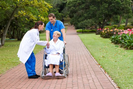 greets: doctor greets wheelchair patient outdoors