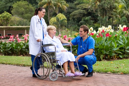 doctor pushing patient in wheelchair in park photo