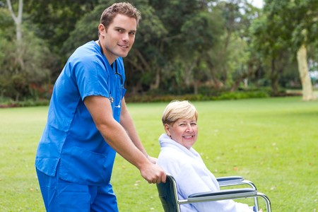 bushes: male nurse pushing wheelchair patient Stock Photo