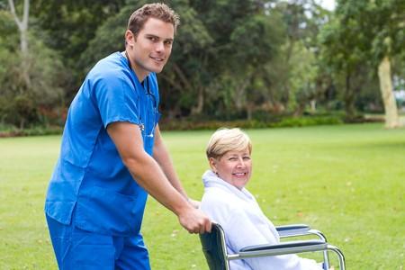chorowity: pÅ'ci mÄ™skiej pielÄ™gniarka pushing wózek inwalidzki pacjenta  Zdjęcie Seryjne