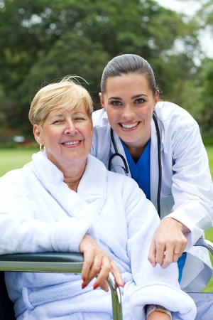garden staff: portrait of happy patient and nurse outdoors Stock Photo