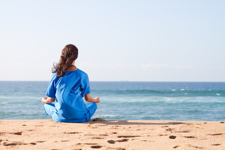 nurse meditating on beach Stock Photo - 7013554