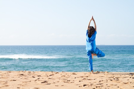 moves: young resident doing yoga moves on beach