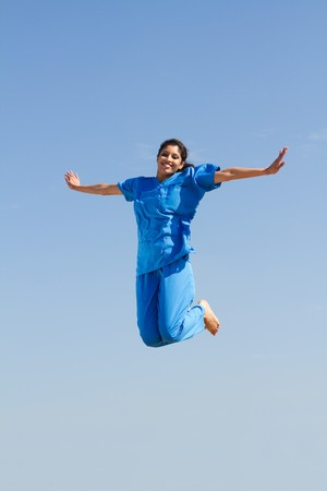 young nurse jumping in air photo
