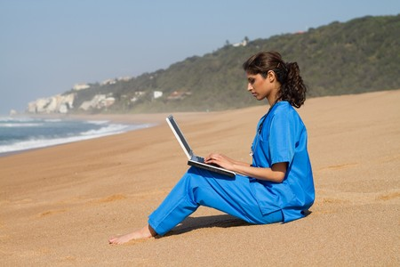 nurse computer: intern using laptop on beach