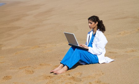 indian doctor using laptop on beach  photo