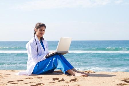 nurse practitioner: pretty indian intern using laptop on beach Stock Photo