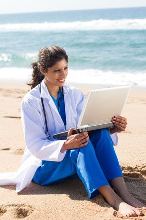 pretty nurse using laptop on beach photo
