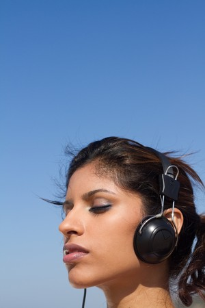 close-up of pretty woman listening to music photo