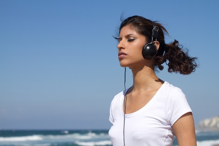 peaceful indian woman listening to music on beach photo