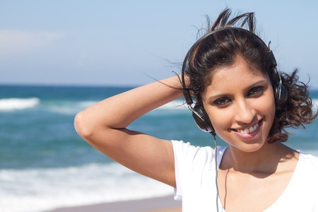 indian woman listening to music on beach photo