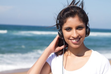 young woman listening to music on beach photo
