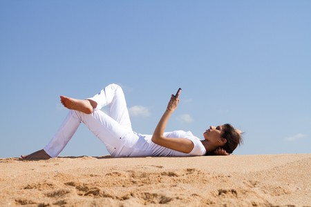 young woman on beach reading book photo
