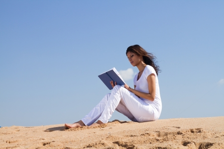 young woman reading book on beach photo