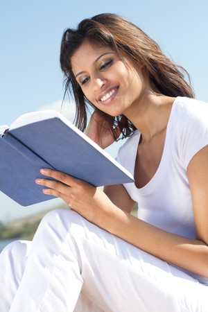 relaxed indian woman reading on beach photo