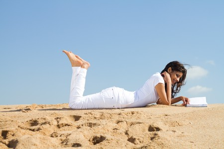 woman relaxing on beach with book photo