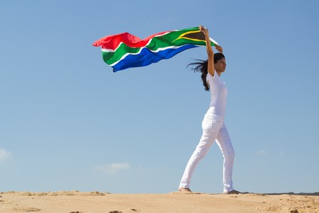 happy woman on beach with south african flag photo