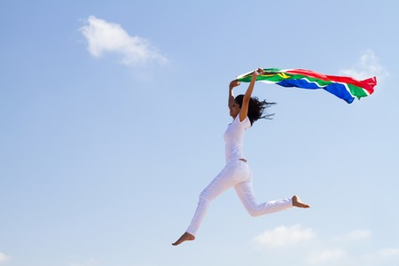 woman soaring in sky with south african flag photo