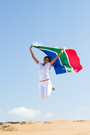 south african flag: young woman jumping with south african flag