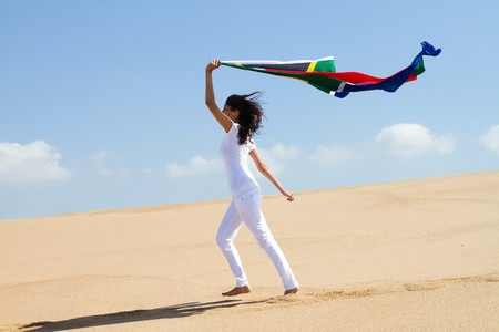 pretty woman holding south african flag on beach photo